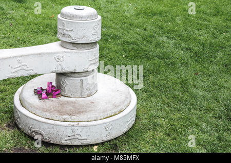 two small children's sandals placed on a concrete block - Stock Photo