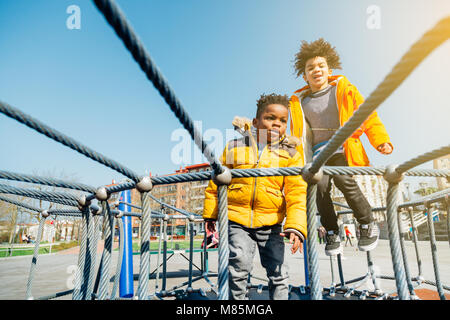 Two children with yellow coats jumping on elastic bed in a playground in a sunny day - Stock Photo