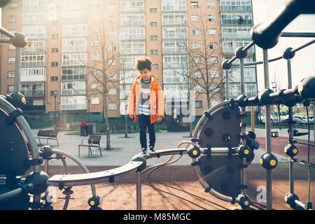Cute little boy walking the balance bar in an urban playground in a sunny day - Stock Photo