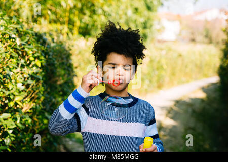Little boy blowing bubbles on a path in the garden on a sunny day - Stock Photo
