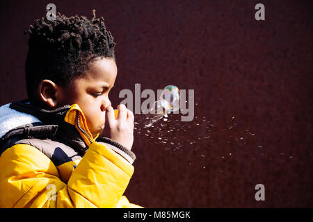 Little boy with yellow coat blowing bubbles on the street in a sunny day - Stock Photo
