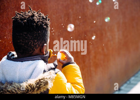 Little boy with yellow coat blowing bubbles on the street in a sunny day. Back view - Stock Photo