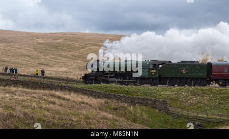 Puffing steam, iconic locomotive LNER class A3 60103 Flying Scotsman travels past rail fans - by Ribblehead Viaduct, - Stock Photo
