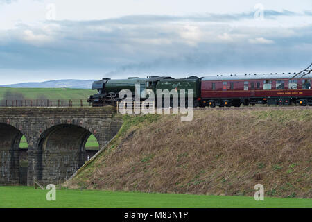 Puffing steam cloud, iconic locomotive LNER class A3 60103 Flying Scotsman about to cross stone bridge - Ribblehead, - Stock Photo