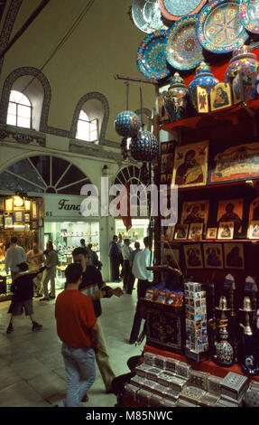 Istanbul Turkey People Shopping In Grand Bazaar Religious Icons And Ceramics Stall Men Talking - Stock Photo