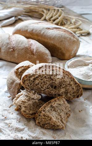 Whole grain bread  and flour on light background. Ceramic bowl full of whole grain flour - Stock Photo