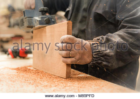 Carpenter using the electric sandpaper on a piece of wood - Stock Photo