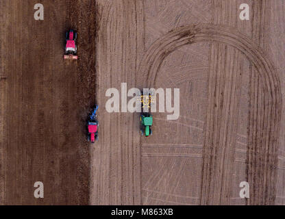 Huaxian. 14th Mar, 2018. Aerial photo taken on March 14, 2018 shows agricultural machineries ploughing the field - Stock Photo