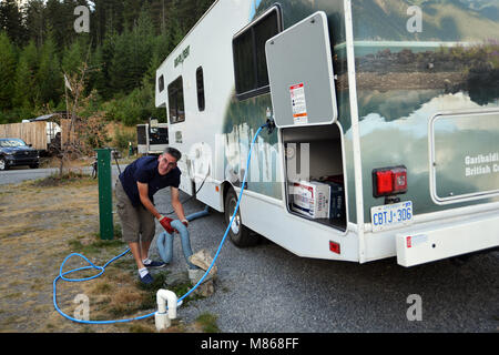 RV vacation Canadian Rockies, Canada man empties dump tank on  holiday model released - Stock Photo