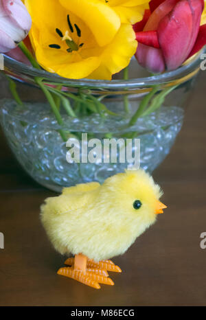 Toy baby chicken, vase, and flowers, 2017. - Stock Photo