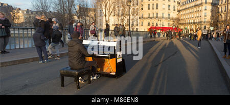 Pianist Louis Artson preforming on a Yamaha piano on the Pont Saint Louis in Paris, France. - Stock Photo