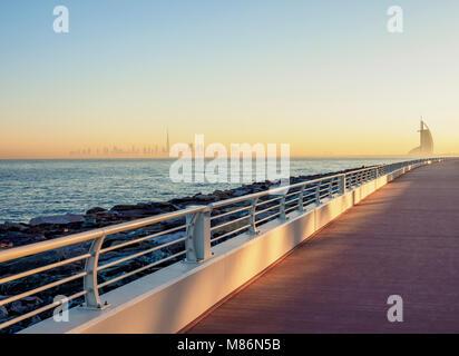 Palm Jumeirah Boardwalk and City Centre Skyline at sunrise, Dubai, United Arab Emirates - Stock Photo