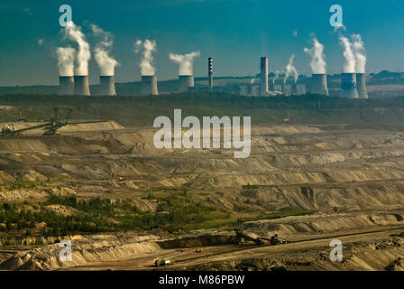 Cooling towers and chimney stacks at Turow thermal power plant over open-pit brown coal mine near Bogatynia in Lower Silesia region, Poland
