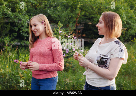 Mother and daughter picking flowers in a garden - Stock Photo