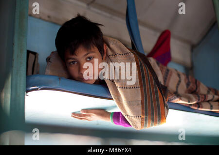 Young Indian boy laying on overhead department, traveling in train looking to camera. He is wearing purple sweather - Stock Photo