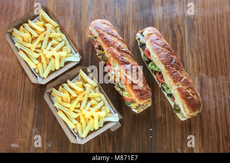 Extra large mighty sandwiches with box of potato french fries meal for two - Stock Photo
