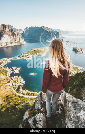 Woman tourist traveling in Norway standing on cliff mountain aerial view Lofoten islands lifestyle exploring concept - Stock Photo