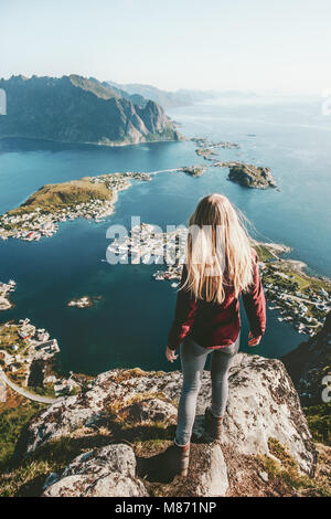 Young woman in Norway standing alone on cliff  mountain lifestyle exploring concept adventure outdoor summer vacations - Stock Photo