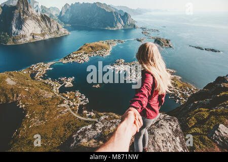 Traveling Couple follow holding hands on cliff mountain in Norway lifestyle concept summer vacations outdoor Lofoten - Stock Photo