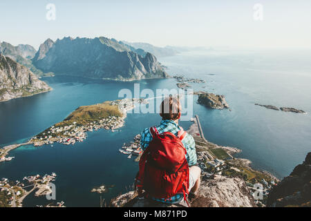 Man sitting on cliff edge alone enjoying aerial view backpacking lifestyle travel adventure outdoor summer vacations - Stock Photo
