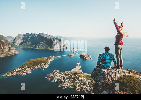 Couple travelers traveling together on top cliff Reinebringen mountain in Norway man and woman family lifestyle - Stock Photo