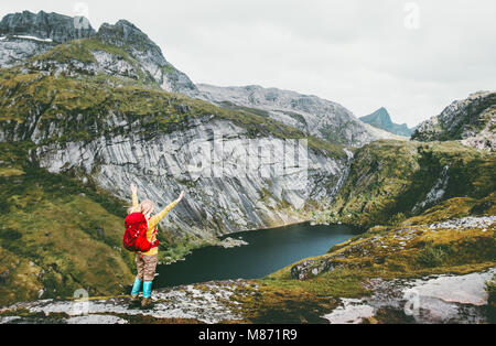 Happy woman raised hands with backpack hiking at lake in mountains of Norway Travel lifestyle adventure success - Stock Photo
