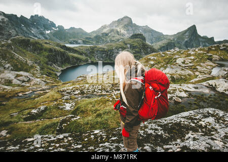 Tourist woman with red backpack hiking in mountains Norway Traveling lifestyle adventure concept active vacations - Stock Photo