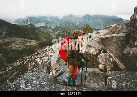 Traveler woman with backpack on Hermannsdalstinden mountain summit in Norway Travel Lifestyle wanderlust concept - Stock Photo