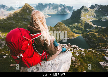 Tourist woman relaxing alone with backpack in mountains Norway Traveling healthy lifestyle adventure concept summer - Stock Photo
