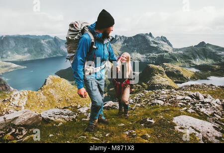 Couple backpackers hiking in Norway mountains love and travel holding hands family together Lifestyle concept vacations - Stock Photo