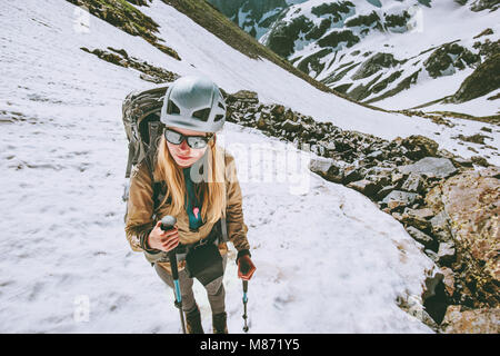 Climber woman hiking in mountains with backpack and helmet gear Traveling lifestyle adventure concept active extreme - Stock Photo