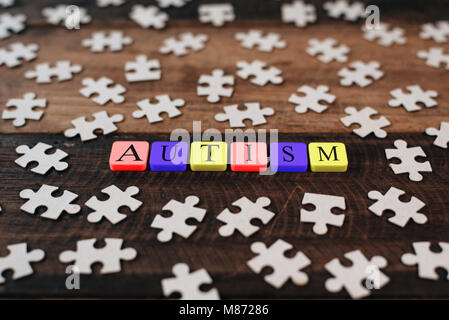 Colourful jigsaw puzzle and alphabet tiles with AUTISM word. Autism concept - Stock Photo