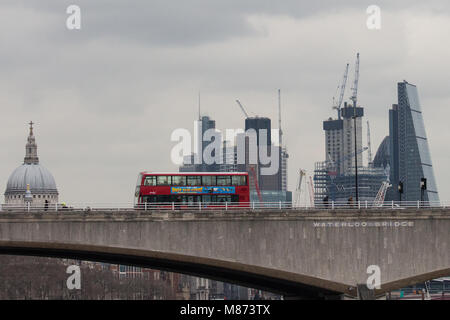 London, UK. 13th March, 2018. A doubledecker bus crosses Waterloo bridge on a cloudy day with St Paul's Cathedral - Stock Photo