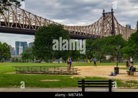 Sunday morning baseball being played in a city park below the 59th St Queensboro Bridge,Long Island City ,Queens - Stock Photo
