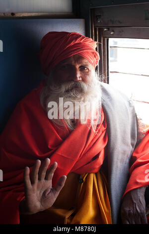 Portrait of an old Indian holy man - sadhu traveling in train, sitting next to window sending his blessings with - Stock Photo