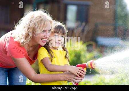 Portrait of gardener woman with daughter watering flowers on the lawn near cottage. - Stock Photo