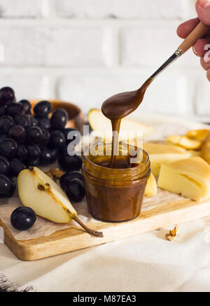 Honey flows from spoon into jar on wooden Board with fruit and cheese - Stock Photo