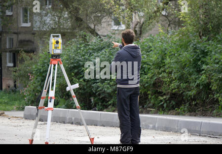 a worker stands next to the level - Stock Photo