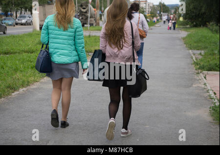 Two girls girlfriend, or mother and daughter are on the road hand in hand with fashionable backpack walking along - Stock Photo