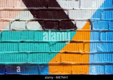 Abstract detail of brick wall with fragment of colorful graffiti. Urban Art close-up, for background use. - Stock Photo