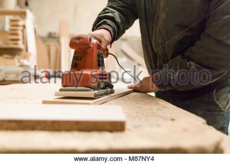 Carpenter using de handsaw in his workshop - Stock Photo