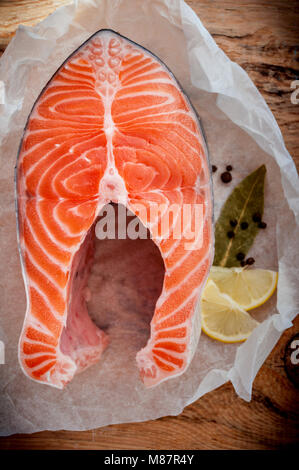 Raw salmon fish steak with lemon and spices on wooden rustic background. Fresh fish. Top view - Stock Photo
