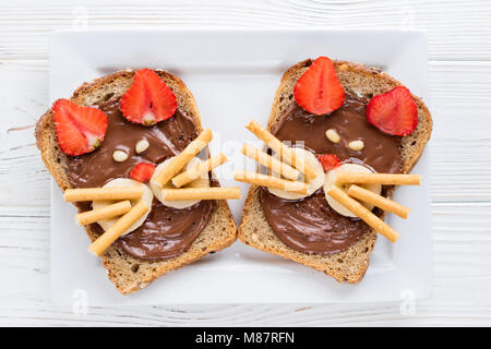 Children's breakfast with sandwiches and milk. Funny cats face sandwiches with berry, chocolate, banana, nuts. Top - Stock Photo