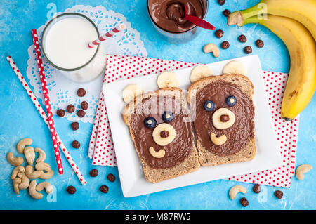 Kids breakfast with sandwiches and milk. Funny bear face sandwiches with chocolate paste, banana, nuts, and berries. - Stock Photo