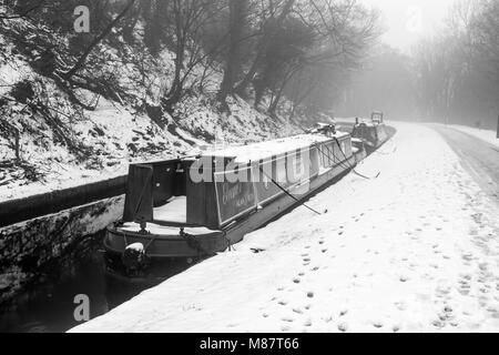 Narrowboats covered in snow are seen moored up on the Llangollen Canal in late winter - Stock Photo