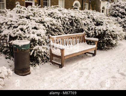 Public litter bin and park bench victorian houses behind covered with snow London winter - Stock Photo