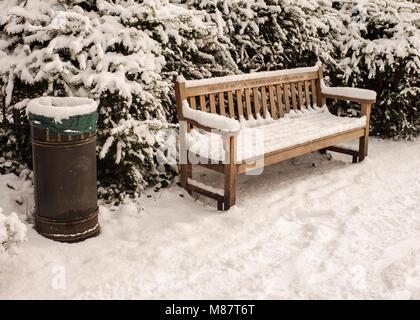 Public litter bin and park bench covered with snow London winter - Stock Photo