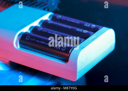 Rechargeable battery being charged. Quick AA Charger - Stock Photo