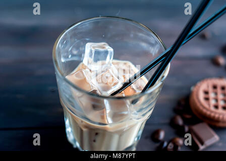 coffee with ice in a glass,milk poured into a glass ice cubes, pieces of chocolate and cookies on a dark wooden - Stock Photo