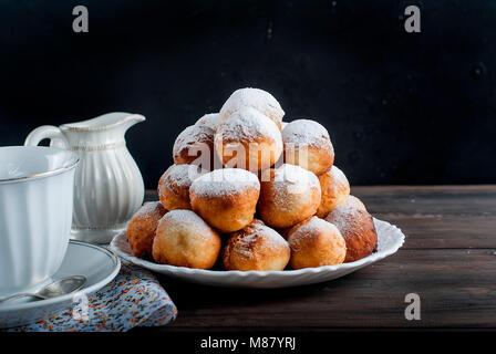 sweet donuts laid out pyramid sprinkled with powdered sugar on the plate , Milk jug and cup, breakfast , on dark - Stock Photo